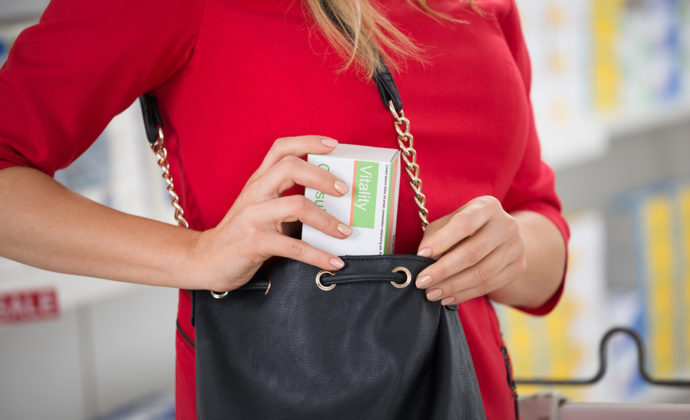 Midsection of woman stealing capsule packet at supermarket
