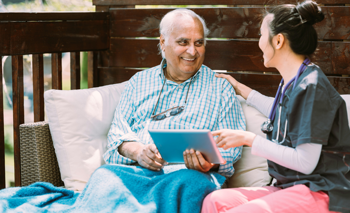 Senior Indian man and Asian female healthcare worker sitting at the garden patio  of the residence. THey are both talking about digital tablet in his lap.